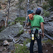 climbing guide Brett Bloxom assess the climb for a night of cliff camping in Estes Park, Colorado.