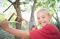 Boy (7-9) using slingshot