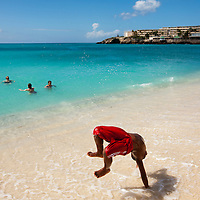 Dutch Antilles, Sint Maarten, Young boy cartwheels in surf at Sunset Beach near Princess Juliana International Airport