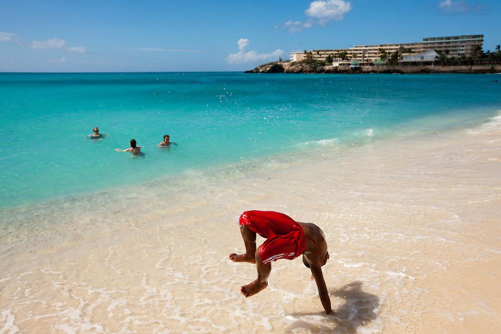 Dutch Antilles, Sint Maarten, Young boy cartwheels in surf at Sunset Beach near Princess Juliana International Airport