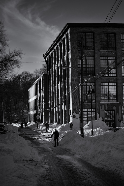 The morning after a blizzard residents shovel along Oella Ave. in front of the Dicky Mill.