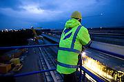 Frankfurt am Main | 07.05.2010..Sie Autobahn A3 am Flughafen Frankfurt wird ab dem 7. Mai 2010 in zehn Naechten voll gesperrt, da eine Betonbruecke errichtet wird, ueber die Flugzeuge zur neuen Start- und Landebahn im Kelsterbacher Wald rollen sollen..Hier: Die A3 kurz vor der Sperrung, die Kraene zum Aufbau der Bruecke rollen heran, ein Bauarbeiter betrachtet die Baustelle...Foto: peter-juelich.com..[No Model Release | No Property Release]
