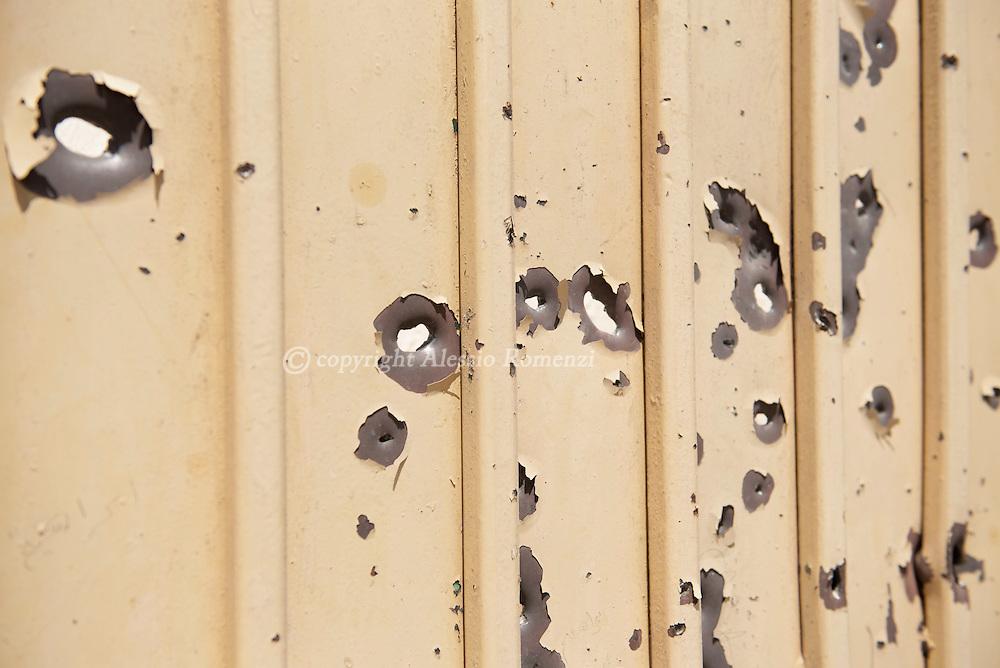 Libya: Particular of a riddled by gunshots gate in 700 neighbourhood in Sirte. Alessio Romenzi