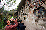 Tourist photographs Anicca, God of Destiny holds wheel of life, Dazu rock carvings, Mount Baoding, China