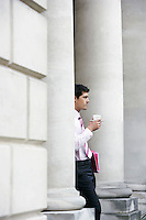 Businessman leaning on pillar outside building holding coffee