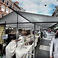Nederland, Amsterdam , 5 oktober 2014.<br /> Het is de bekendste markt van Nederland, maar deze zondag zullen veel bezoekers waarschijnlijk toch echt even moeten wennen aan wat ze aantreffen op de Albert Cuyp. De kramen, sinds mensenheugenis opgesteld langs de stoepen, worden voor &eacute;&eacute;n dag verplaatst naar het midden van straat.<br /> Ruggelings staan ze dan, waardoor bezoekers niet meer alleen maar zicht hebben op de kramen, maar ook de achterliggende winkels. Die worden daarbij meer bij de straat betrokken, is het idee.Een upgrade, zegt stadsdeel Zuid. Een riskant plan, zeggen marktkoopmannen. Er zijn voordelen en er zijn nadelen, zegt de marketingafdeling van de markt zelf. Hoe dan ook wordt er al jaren over gesteggeld. Zondag zal veel duidelijk worden, als bezoekers, ondernemers en ook bewoners uitvoerig zullen worden gevraagd naar hun mening. Stadsdeelbestuurder Paul Slettenhaar benadrukt de markt niets te willen opleggen. 'Deze opstelling lijkt ons een goed idee - ook wij willen de markt nog beter maken. Maar als blijkt dat het niet goed uitpakt, zetten we het natuurlijk niet door.'<br /> Foto:Jean-Pierre Jans
