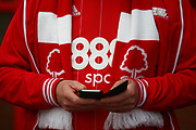 A Nottingham Forest fan look at his mobile phone during the EFL Sky Bet Championship match between Nottingham Forest and Burton Albion at the City Ground, Nottingham, England on 21 October 2017. Photo by John Potts.