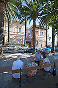 Place du Marechal Foch. Old men having a chat in front of the Musee Napoleonien.
