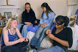 Multiracial group of teenage girls sitting together in bedroom painting nails and chatting,