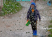A South African boy walks through the rain in the informal shack settlement of Masiphumelele outside Cape Town, South Africa.