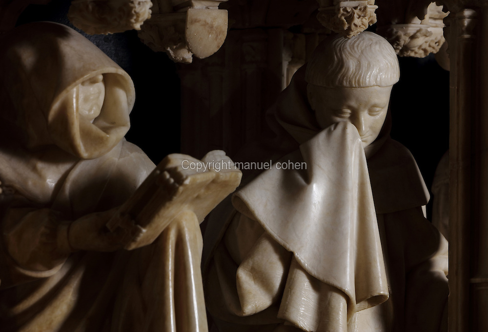 Sculptures of weepers, including a man drying his eyes with a handkerchief, by Claus Sluter, 1340-1405, and Claus de Werve, 1380-1459, on the tomb of Philippe le Hardi, or Philip the Bold, 1342-1404, (Philippe II, duc de Bourgogne, or Philip II, Duke of Burgundy), 1381-1410, in the Grande Salle du Palais des ducs de Bourgogne, or Salle des Gardes, a 15th century Flamboyant Gothic hall, in the Musee des Beaux-Arts de Dijon, opened 1787 in the Palace of the Dukes of Burgundy in Dijon, Burgundy, France. The tomb consists of a painted alabaster effigy with lion and angels, and below, figures of pleurants or weepers among Gothic tracery. Claus Sluter worked on the weepers 1389-1404 and produced startlingly realistic sculptures, and Claus de Werve completed them 1404-10. The tombs were originally from the Chartreuse de Champmol, or Chartreuse de la Sainte-Trinite de Champmol, a Carthusian monastery which was sacked in the French Revolution and the tombs moved to Dijon cathedral then here in 1827. Picture by Manuel Cohen