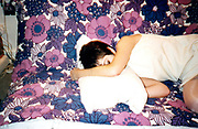 Young woman sleeping on top of a floral duvet.