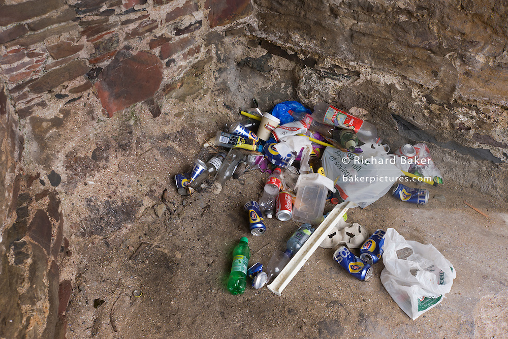 Beer cans and other rubbish collects in a corner of a heritage structure on the beach at Croyde, north Devon.