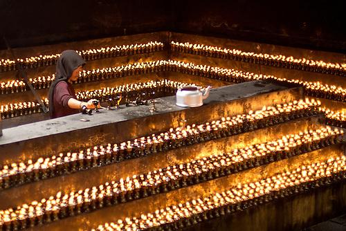 A Tibetan nun lights hundreds of prayer candles at The Jokang Tibetan Buddhismu0027s most holy. & Tibetan Nun Lighting Butter Candles | Neil Wade Photography azcodes.com