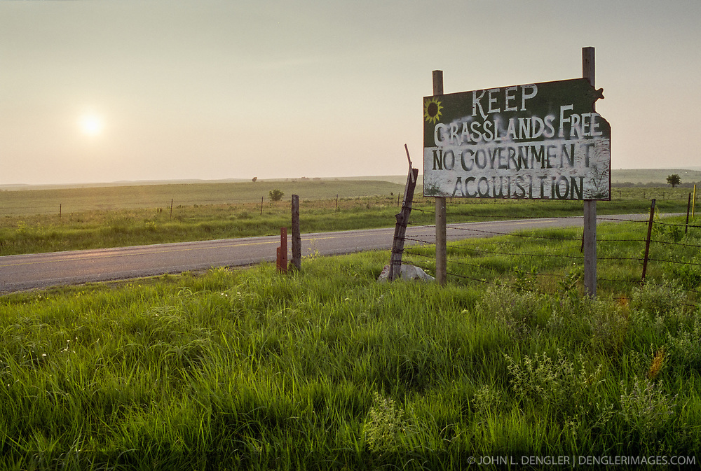 This 1997 photograph of a sign just outside Cottonwood Falls on Kansas Highway 177 is an example of the controversy that surrounded the formation of the nearby Tallgrass Prairie National Preserve, formerly the Z-Bar Ranch. <br /> <br /> Initially, the Flint Hills communities surrounding the proposed park were supportive, but then opposition developed. According to National Park Service document &quot;Tallgrass Prairie National Preserve Legislative History, 1920-1996&quot; most local business owners were supportive but many ranchers had overall concerns about federal involvement and federal land ownership with some ranchers specifically concerned about land being lost by eminent domain. The park proposal became a divisive and heated issue between the two community groups.<br /> <br /> In the end, an unique compromise was reached with a public/private partnership between the National Park Service and The Nature Conservancy. Today, the 10,894-acre Tallgrass Prairie National Preserve is the only unit of the National Park Service dedicated to the preservation of the tallgrass prairie ecosystem.<br /> <br /> According to a National Park Service study, 13,548 non-local visitors in 2013 fueled $849,400 in spending at the Tallgrass Prairie National Preserve and in communities near the park.