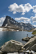 A female hiker is resting at the lake Geisspfadsee with the peaks of the Rothorn and the Schwarzhorn, Landschaftspark Binntal, Valais, Switzerland