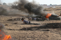 October 5, 2018 - Al-Buraj Refugee Camp, The Gaza Strip, Palestine - Palestinian protesters set fire to tires and throw rocks, while Israeli forces opened live fire and tear-gas bombs east of Al-Buraj refugee camp in central of the Gaza Strip, Two Palestinians killed and dozens wounded during clashes between Palestinians and Israeli troops. (Credit Image: © Hassan Jedi/Quds Net News via ZUMA Wire)
