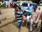 05 JULY 2017 - POIPET, CAMBODIA: A porter in Poipet pushes the belongings of Cambodian migrant workers who left Thailand to a bus stop. The Thai government proposed new rules for foreign workers recently. The new rules include fines of between 400,000 and 800,00 Thai Baht ($12,000 - $24,000 US) and jail sentences of up to five years for illegal workers and people who hire illegal workers. Hundreds of companies fired their Cambodian and Burmese workers and tens of thousands of workers left Thailand to return to their countries of origin. Employers and human rights activists complained about the severity of the punishment and sudden implementation of the rules. On Tuesday, 4 July, the Thai government suspended the new rules for 180 days and the Cambodian and Myanmar governments urged their citizens to stay in Thailand, but the exodus of workers continued through Wednesday.     PHOTO BY JACK KURTZ