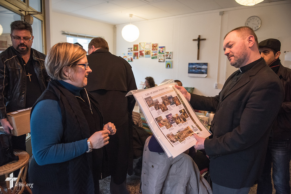 Deaconess Pam Nielsen of LCMS Communications presents on behalf of Concordia Publishing House posters to the Rev. Markus Fischer, pastor of the Evangelisch-Lutherische St. Trinitatisgemeinde, a SELK Lutheran church in Leipzig, Germany, during a Bible Study for refugees on Friday, Nov. 13, 2015, near the church in Leipzig. LCMS Communications/Erik M. Lunsford