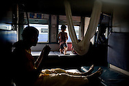 A mother ties a cloth cradle to the upper berths for her child (background) while waiting at Chandrapur Stn., Maharashtra, in the Himsagar Express 6318 on 8th July 2009.. .6318 / Himsagar Express, India's longest single train journey, spanning 3720 kms, going from the mountains (Hima) to the seas (Sagar), from Jammu and Kashmir state of the Indian Himalayas to Kanyakumari, which is the southern most tip of India...Photo by Suzanne Lee / for The National