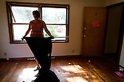 MILWAUKEE, WI — AUGUST 8, 2014: Cherri Harsh with ECH Property Management removes blackout curtains from an evicted apartment unit at 2901 Atkinson Avenue in Milwaukee. The tenant had previously moved out the majority of their items, leading to a quick eviction for movers and Milwaukee County detectives.