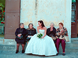beautiful bride sitting on a bench with local older woman in Italy as they talk and laugh together