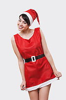 Portrait of smiling young woman in Santa outfit over white background