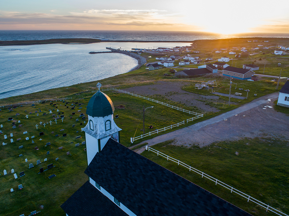 Canada, Newfoundland, Codroy, Aerial view of church and graveyard in fishing village on summer evening