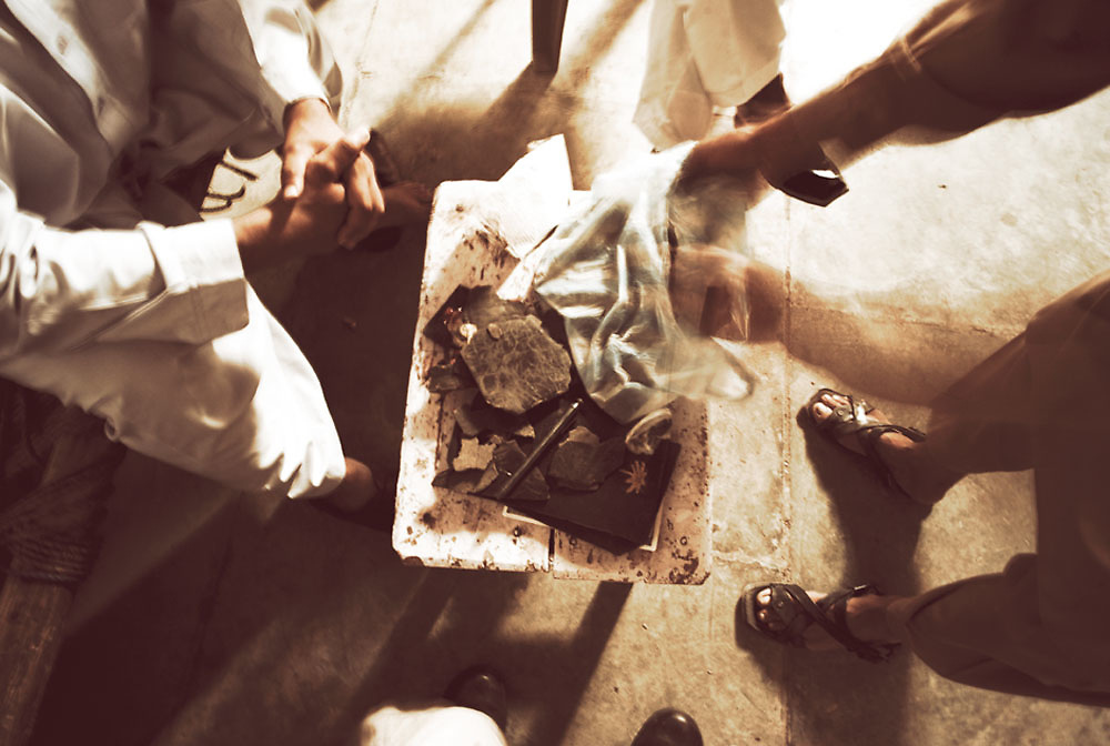 Men circle around to view a bag of hash emptied out onto a table at the Smuggler's Bazaar, Khyber-Pakhtunkhwa, Pakistan on 25th Sep, 2007....