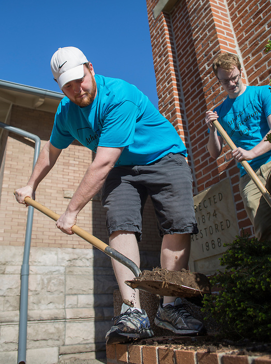 Stuart Randle, left, a senior studying computer engineering, and Evan Gass, right, a senior studying mechanical engineering, shovel out dirt in preparation of taking out a bush in front of City Hall during Athens Beautification Day on April 17, 2016.