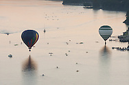 Poughkeepsie, New York -  Hot air balloons take off from the Hudson River Rowing Association Boathouse on the banks of the Hudson River on July 6, 2014. The balloon festival is organized by the Dutchess County Regional Chamber of Commerce.