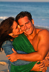 woman playfully biting man's ear at the beach in East Hampton, NY
