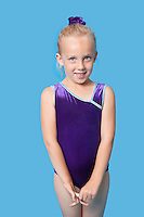 Portrait of a happy young female gymnast standing over blue background