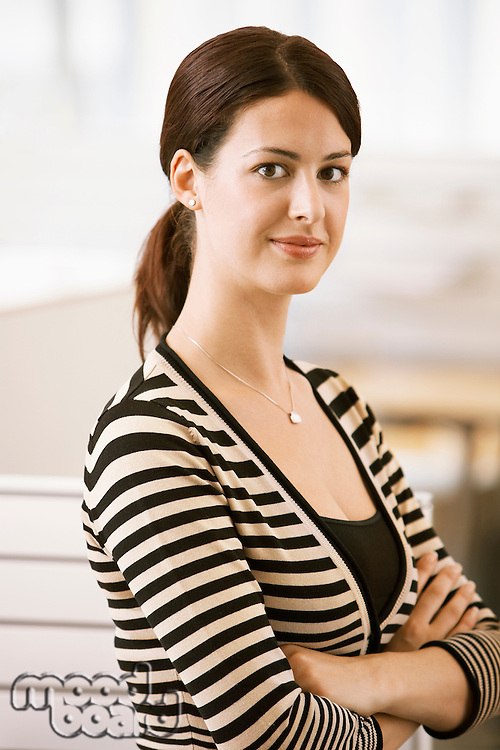 Mid-adult female office worker leaning on cubicle portrait