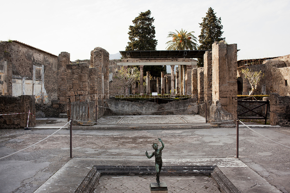 POMPEII, ITALY - 4 APRIL 2013:    A statue of the Faun is seen here in the House of the Faun in Pompeii, Italy, on April 4th, 2013. With its 2,970 square meters (31,978 square feet) , the House of the Faun is the largest house in Pompeii.<br /> <br /> In recent years, a series of collapses at the site have alarmed conservationists, who warn that the ancient Roman city is dangerously exposed to the elements ? and poorly served by the red tape, lack of strategic planning and limited personnel of the site's historically troubled management. <br /> <br /> Pompeii, along with Herculaneum, was buried under 4 to 6 meters (13 to 20 ft) of ash and pumice in the eruption of Mount Vesuvius in 79 AD. After its initial discovery in 1599, Pompeii was rediscovered as the result of intentional excavations in 1748 by the Spanish military engineer Rocque Joaquin de Alcubierre.<br /> <br /> Pompeii is an UNESCO World Heritage Site and one of the most popular tourist attractions of Italy, with approximately 2.5 million visitors every year.<br /> <br /> Gianni Cipriano for The New York Times