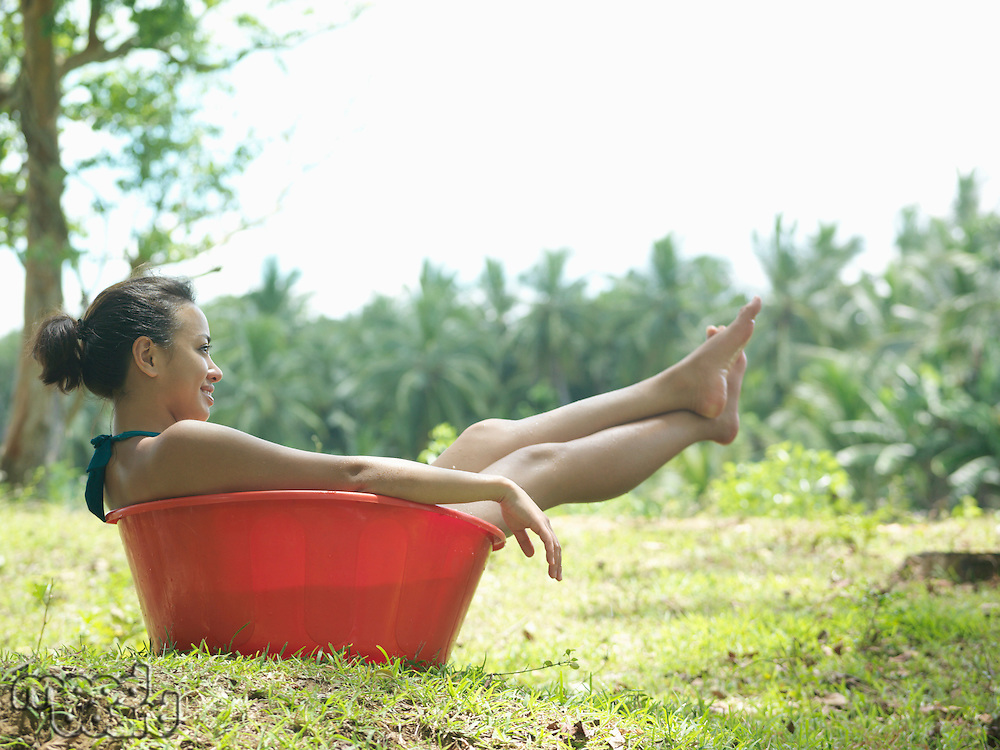 Young woman sitting in bowl outdoors side view smiling