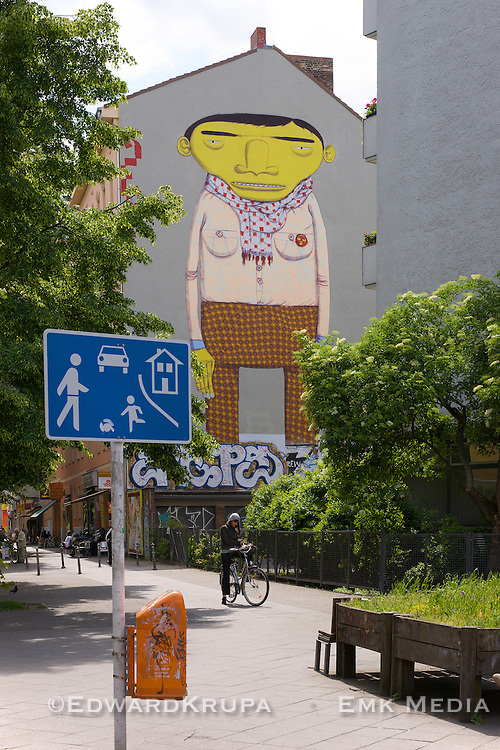 Giant yellow faced man adorns the entire side of of an apartment building. A large piece of street art in the Kreutzberg area of Berlin by the artist Blu.