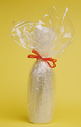 Still life of gift wrapped bottle with a red bow