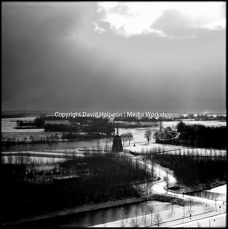 Elevated monochrome view over Dutch snowy winter landscape south of Amsterdam, showing the Amstel river, a canal, farms and villages, and Rembrandt's favorite windmill.