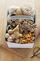 Assorted mushroom in basket on table elevated view
