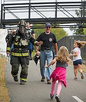 "In full gear weighing approximately 60 lbs. Laconia Firefighter Andy Francis walks the ""Take the Trail Fun Walk"" alongside honorary member Alan Hopkins during the WOW Fest event held Saturday morning.   (Karen Bobotas/for the Laconia Daily Sun)"
