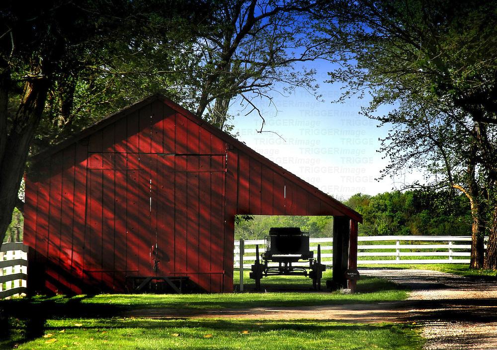 A horse drawn buggy under a barn