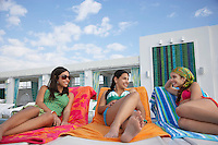 Three teenage girls (16-17) lying on sunloungers