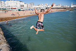 © Licensed to London News Pictures. 07/09/2016. Brighton, UK. Children jump of the Pier and pontoon in the sea as hundreds of people take advantage of the warm weather to spent time on the beach in Brighton. Photo credit: Hugo Michiels/LNP
