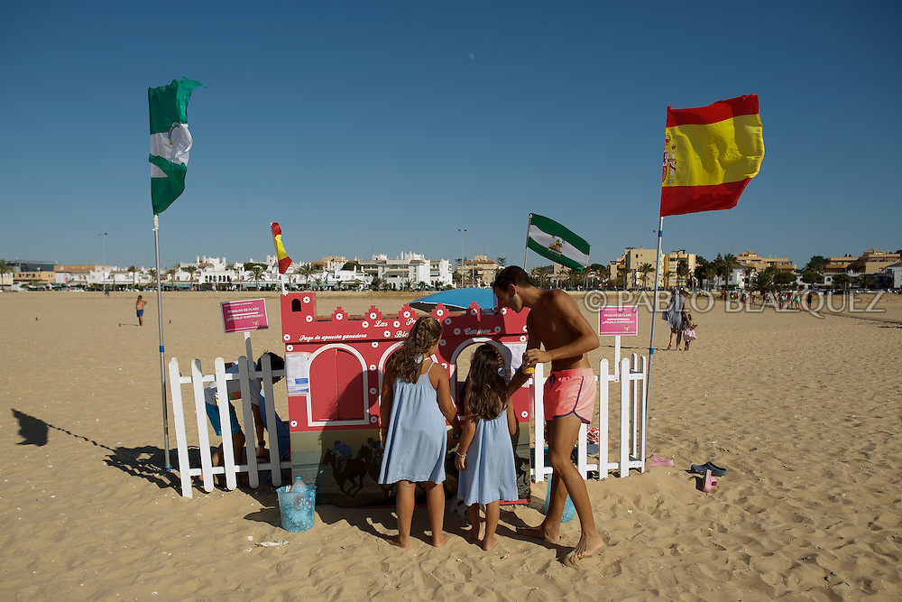 12/08/2016. Children use stalls to stake for sweets during during the beach horse races on August 12, 2016 in Sanlucar de Barrameda, Cadiz province, Spain. Sanlucar de Barrameda yearly horse races traditional origin started with informal races of horse's owners delivering fish from the port to the markets. But the first formal races date back to 1845 and they are the second oldest in Spain, after Madrid. The horse races take place near the Guadalquivir river mouth during August