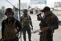 Licensed to London News Pictures. 01/04/2017. Mosul, Iraq. Iraqi Federal Police officers prepare their equipment in West Mosul, Iraq, today (01/04/2017). Iraqi forces continue to fight house to house as they push further into West Mosul. Iraqi forces are now advancing on the city's old districts where Islamic State fighters still hold out. Photo credit: Matt Cetti-Roberts/LNP
