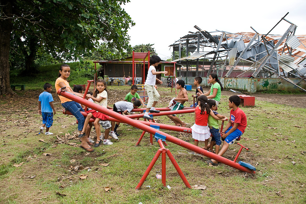 Children play in the playground while a collapsed building sits in the background. Located on the Caribbean coast of Costa Rica, Tortuguero is well known for the nesting turtles on its beaches as well as its diverse wildlife along its rivers banks.