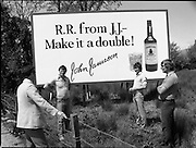 President Reagan Visits Ireland..Advertising Campaign.1984.04.06.1984.06.04.1984.4th June 1984..Availing of the opportunity of the President Reagan visit, the Whiskey manufacturers advertised their wares..Photo shows a large billboard encouraging RR (Ronald Reagan) to have a double. Passers by discuss the billboard..