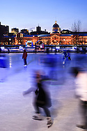 Montreal, Quebec, Canada - January 16, 2011: People at dusk skating on The Quays Skating Rink in the Quays of the Old Port in Montreal on a cold January evening. The skating rink is illuminated with colourful lights at night.