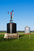 Windmill, water tank and grain silo in farm paddock in rural country Victoria, Australia. <br />